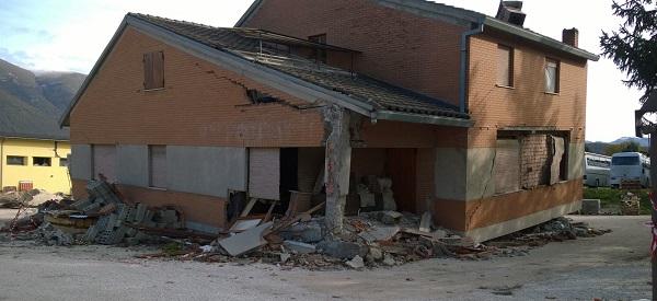 Un edificio pesantemente danneggiato dal sisma nel centro di Norcia. In alto la tendopoli allestita dalla Protezione Civile